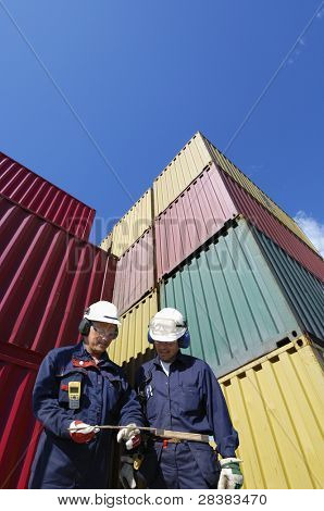 workers, engineers, with large stacks of cargo containers in background.