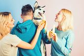 Providing Him Different Vitamins And Minerals. Pet Sitters Feed The Pet. Happy Women And Man Play Wi poster