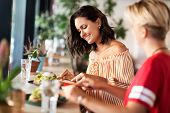 food and people concept - female friends eating at restaurant or cafe poster