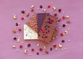 Chocolate On A Violet Background, Surrounded By Nuts And Dried Fruits. Chocolate. Chocolate Bar. Nut poster