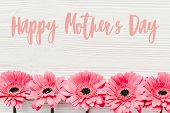 Happy Mothers Day Text Sign At Pink Gerbera On White Wooden Background, Flat Lay. Floral Greeting C poster