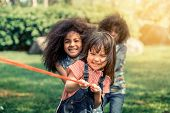 Happy Children Playing Tug Of War And Having Fun During Summer Camping In The Park. Children Recreat poster