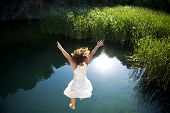 Young woman in white dress jumping into a idyllic lake