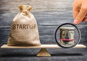 Money Bag With The Word Startup And Dollars On The Scales. Analysis Of Funds Raised And Verification poster