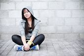 image of leggins  - Young asian girl sitting in urban background - JPG
