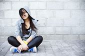 picture of rap-girl  - Young asian girl sitting in urban background - JPG
