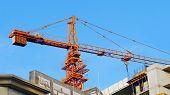 Crane. Construction Crane. Huge Crane And Concrete Building Against Blue Sky. Self-erection Crane. T poster