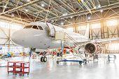 Aviation Hangar With Passenger Aircraft Jet For Maintenance. poster