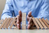 Businessman Hand Stopping Falling Wooden Blocks Or Dominoes. Business, Risk Management, Solution, In poster