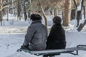A Married Couple Of Pensioners Is On The Gray Bench In The Snow Park In Winter And An Elderly Woman  poster