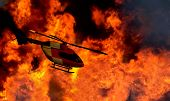 foto of rescue helicopter  - Search and rescue helicopter flying by a bushfire - JPG