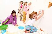 stock photo of slumber party  - Group of elementary children cleaning up after food fight at slumber party with pizza and popcorn - JPG