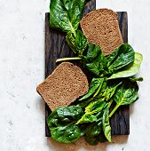 Rye Bread For Sandwiches With Fresh Leaves Of Juicy Spinach On A Wooden Board On A Gray Background.  poster