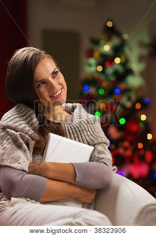 Happy Woman In Chair In Front Of Christmas Tree Hugging Tablet P