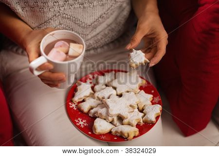 Closeup On Woman Eating Christmas Cookie And Drinking Hot Chocol