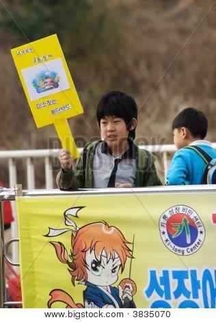 Korean Boy Hold A Sign.