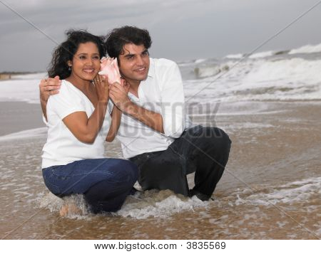 Asian Couple In The Beach Listening To A Conch
