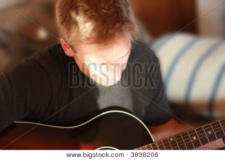 Man Playing Guitar With Head Down