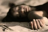 pic of crime scene  - woman playing dead lying in the sand - JPG