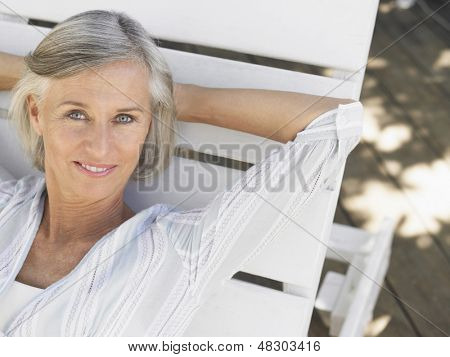 Closeup of a smiling middle aged woman reclining on sunlounger