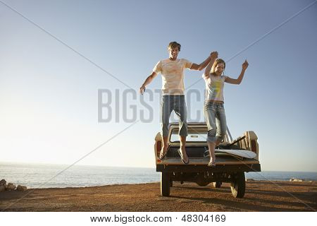 Full length of excited young couple jumping from back of van parked by ocean