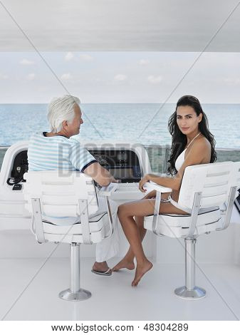 Portrait of young woman with middle aged man sitting at helm of yacht