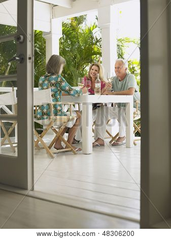 Three middle aged people sitting at verandah table