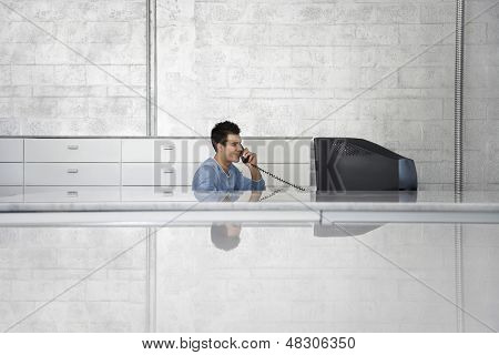 Young businessman sitting at computer desk using landline phone in office