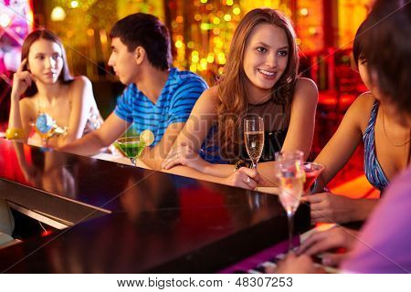 Portrait of pretty girls talking at party in the bar