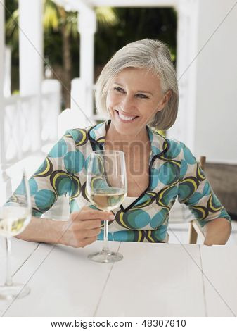 Portrait of a middle aged woman holding glass of wine at verandah table