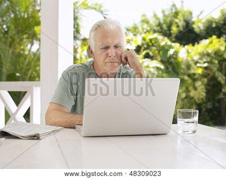 Serious mature man using laptop at verandah table