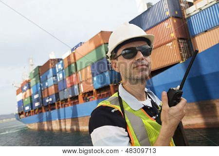Man in hard hat using walkie talkie at container terminal