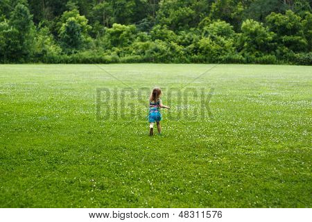 Small child running through field towards woods