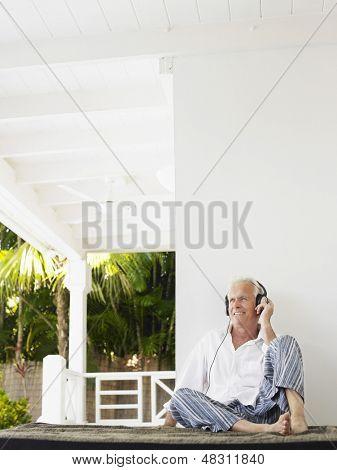 Relaxed mature man wearing headphones on verandah
