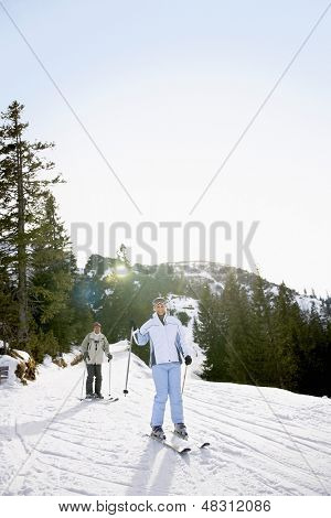 Full length of a couple skiing down slope against trees and sky