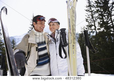 Happy skiing couple in warm clothing with skis against mountains