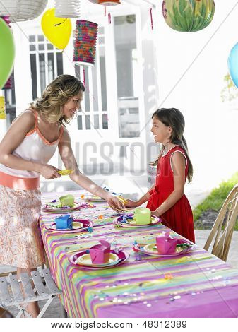 Mother and young daughter setting outdoor table for birthday party