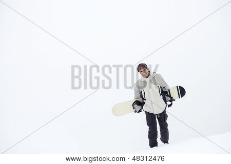 Portrait of a young man walking with snowboard in snow