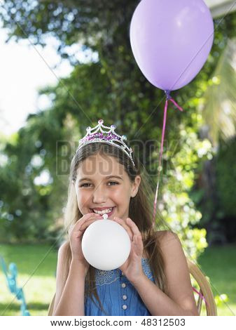 Portrait of smiling young girl wearing tiara and blowing up balloons at birthday party