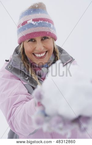 Portrait of a happy young woman holding snowball in winter