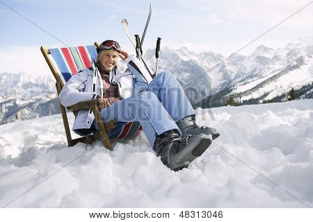 Portrait of a smiling woman sitting on deckchair in snowy mountains
