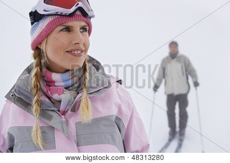 Closeup of a woman with man skiing in background on slope