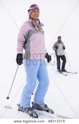 Full length of a female skier with man in background standing on ski slope