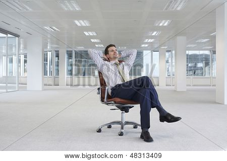 Full length of relaxing young businessman on chair in empty office space