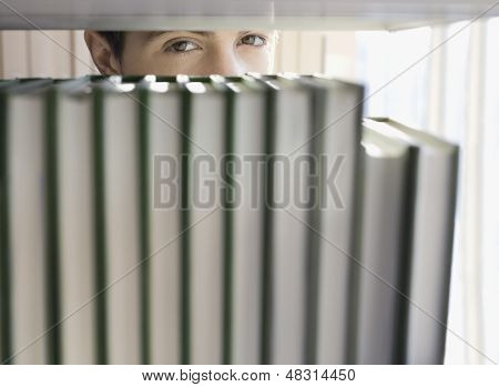 Closeup of a young man peeking from behind books on shelf in library