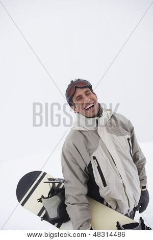 Portrait of a cheerful young man wearing ski goggles with snowboard against sky