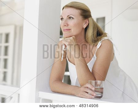 Smiling middle aged woman with water glass on verandah looking away