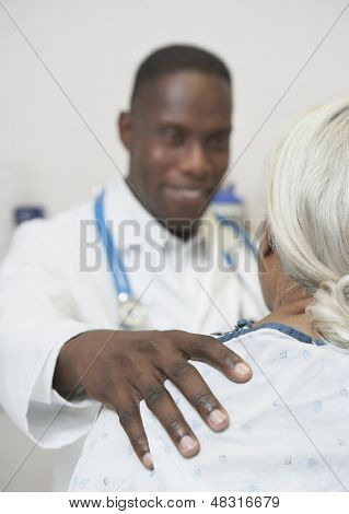 Male doctor reassuring senior patient