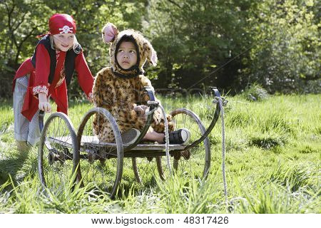 Young boy in pirate costume pushing thoughtful boy in jaguar costume on cart in the garden