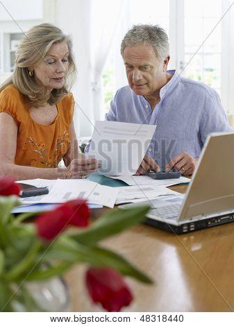 Pareja mirando las cuentas con la calculadora y el ordenador portátil